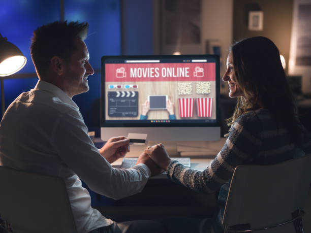 Couple watching movies online together stock photo