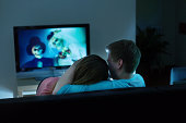 Couple watching Scary Halloween horror movie on TV together at home.