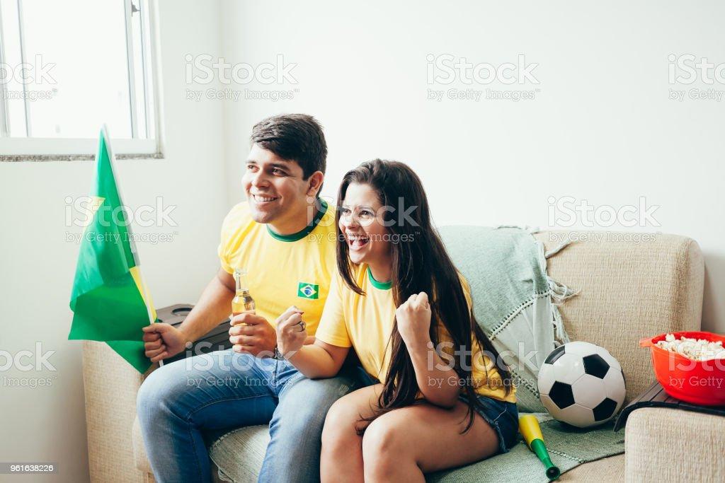 Casal assistindo jogo de futebol na televisão, comemorando gol e gritando - foto de acervo