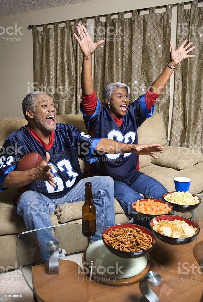 Couple watching sports on TV. stock photo