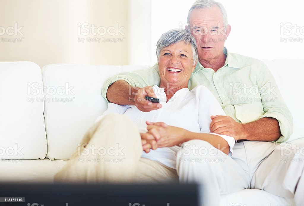 Couple watching television in living room stock photo