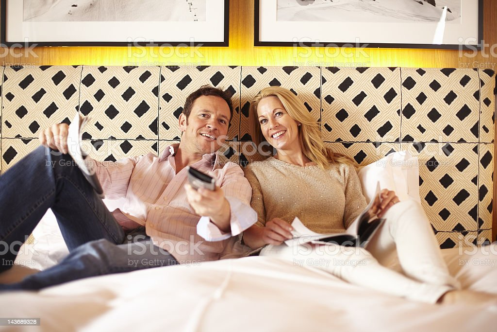 Couple watching television on bed stock photo