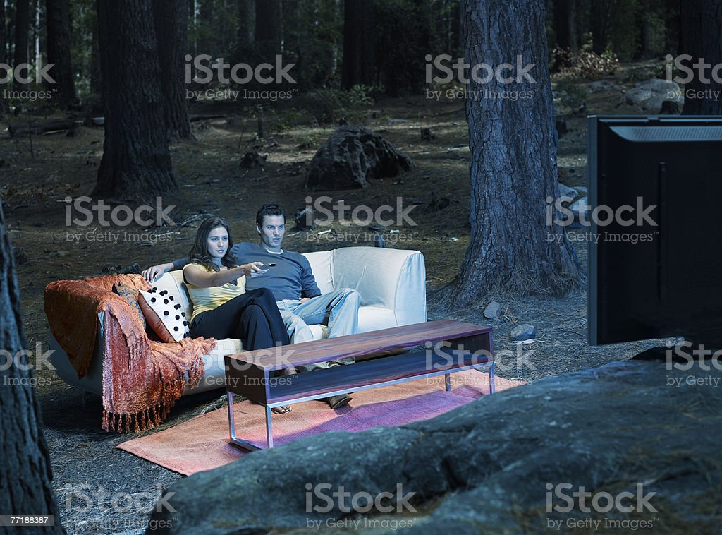 A couple watching television outdoors in the woods stock photo