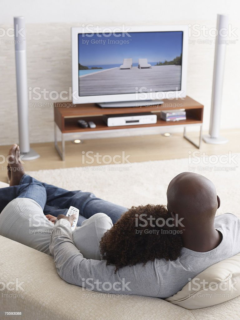 A couple watching television relaxing stock photo