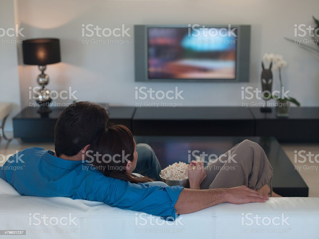 Couple watching television together and eating popcorn stock photo