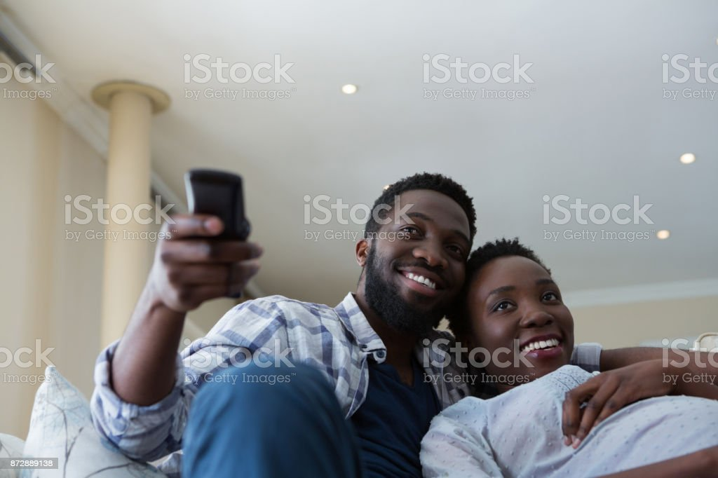 Couple watching television together in living room stock photo