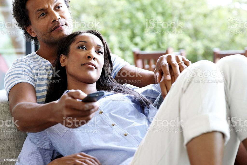 Couple watching television together stock photo
