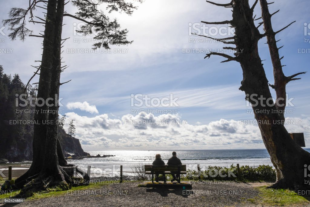 Couple watching the ocean at an Oregon beach stock photo