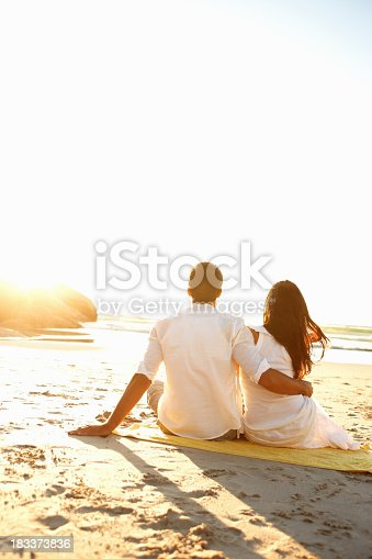 Rear view of couple sitting on towel on beach