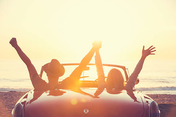 Couple watching the sunset in a convertible car. stock photo