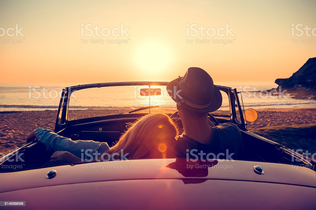 Couple watching the sunset in a convertible car. - Royalty-free Adamlar Stok görsel