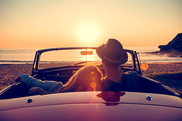 Couple watching the sunset in a convertible car. bildbanksfoto