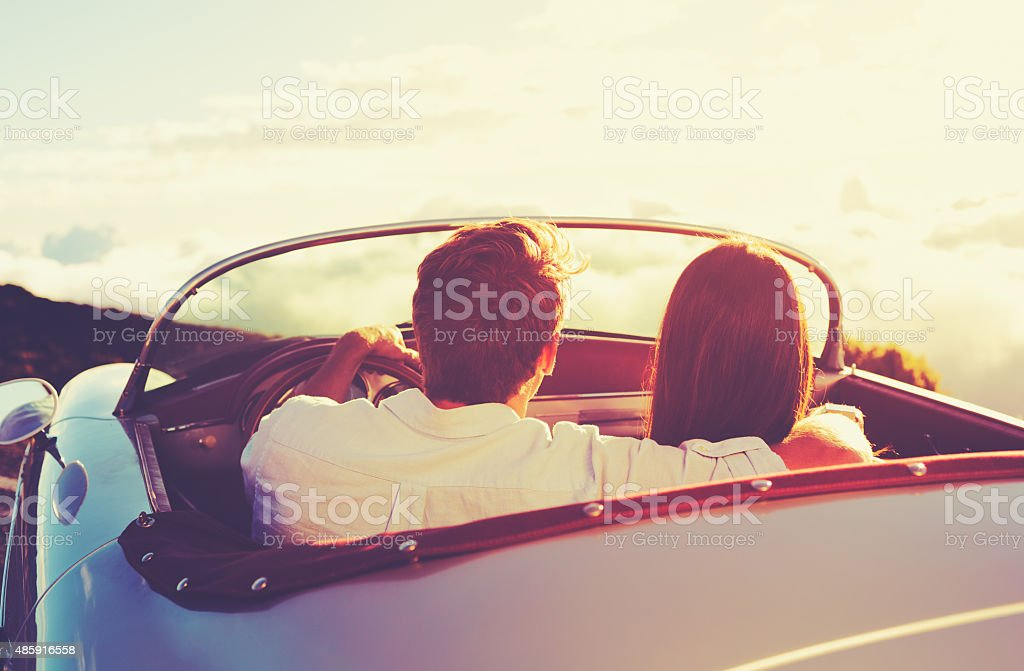Couple Watching the Sunset in Classic Vintage Car stock photo