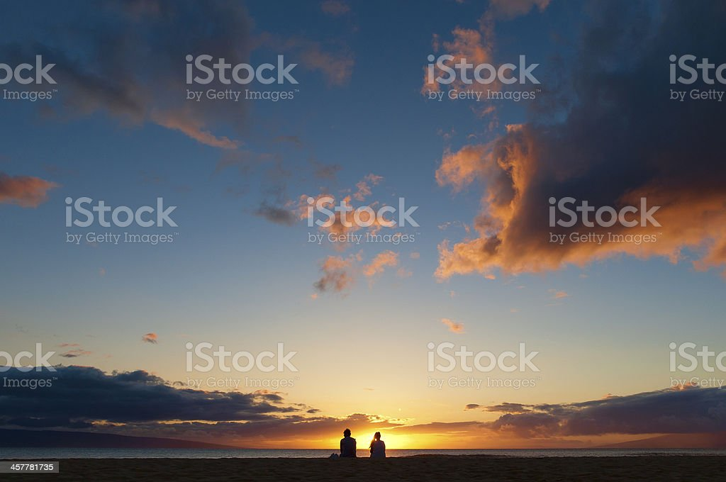 Couple watching the sunset on a beach in Maui, Hawaii. stock photo