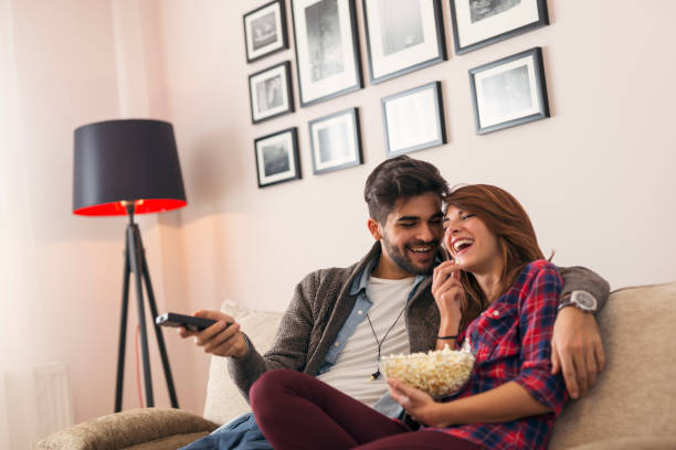 Couple watching TV and eating popcorn stock photo