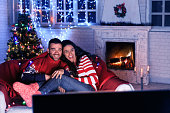 Young couple resting at home and watching TV in front of fireplace.