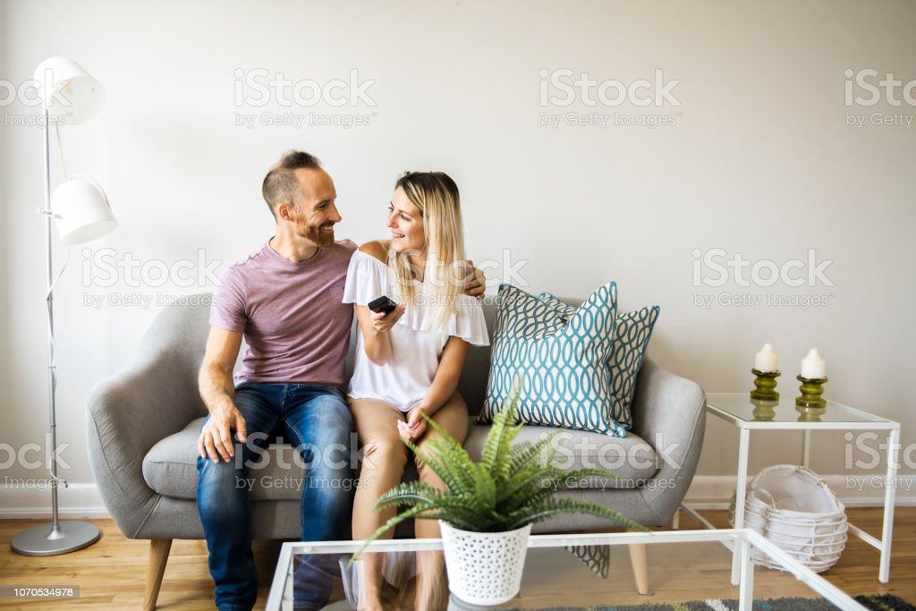A Couple watching tv at home sitting in a comfortable couch in the...