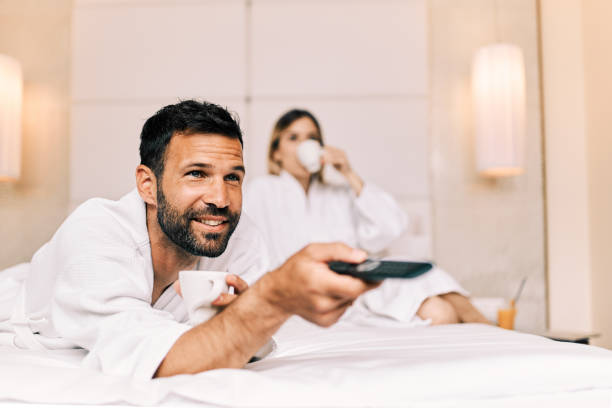 Couple watching TV in a hotel room stock photo