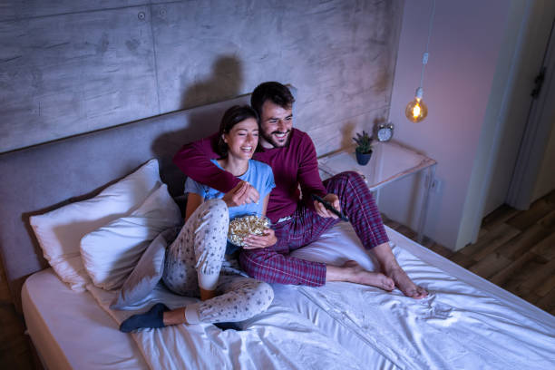 Couple watching TV in bed stock photo