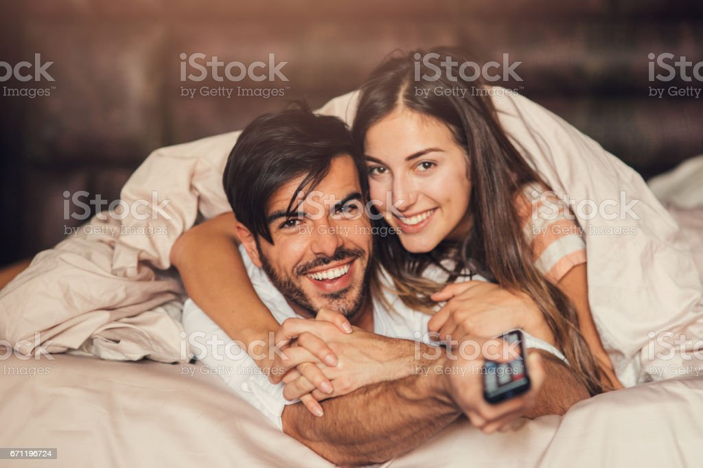 Couple watching TV in bed Couple watching TV in bed. 20-29 Years Stock Photo