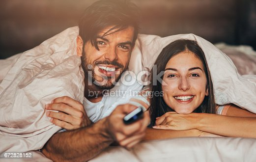 istock Couple watching TV in bed 672828152
