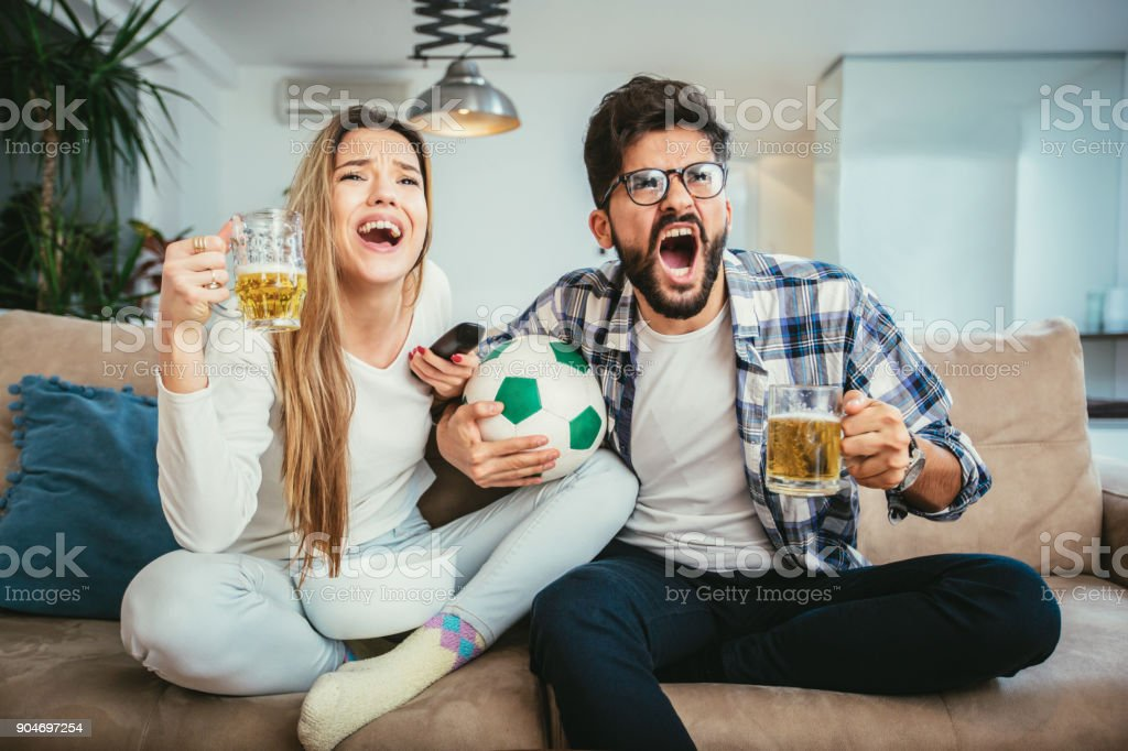 Couple watching tv in living room while eating popcorn and drinking beer stock photo