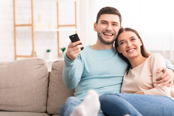 Couple Watching TV Relaxing Sitting On Sofa At Home Weekend. Happy Couple Watching TV Relaxing Sitting On Sofa At Home. Selective Focus, Copy Space cable tv stock pictures, royalty-free photos & images