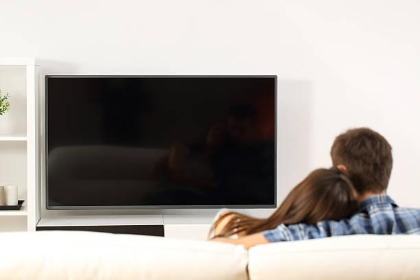 casal assiste a vista de ecrã televisão - tv e familia e ecrã imagens e fotografias de stock