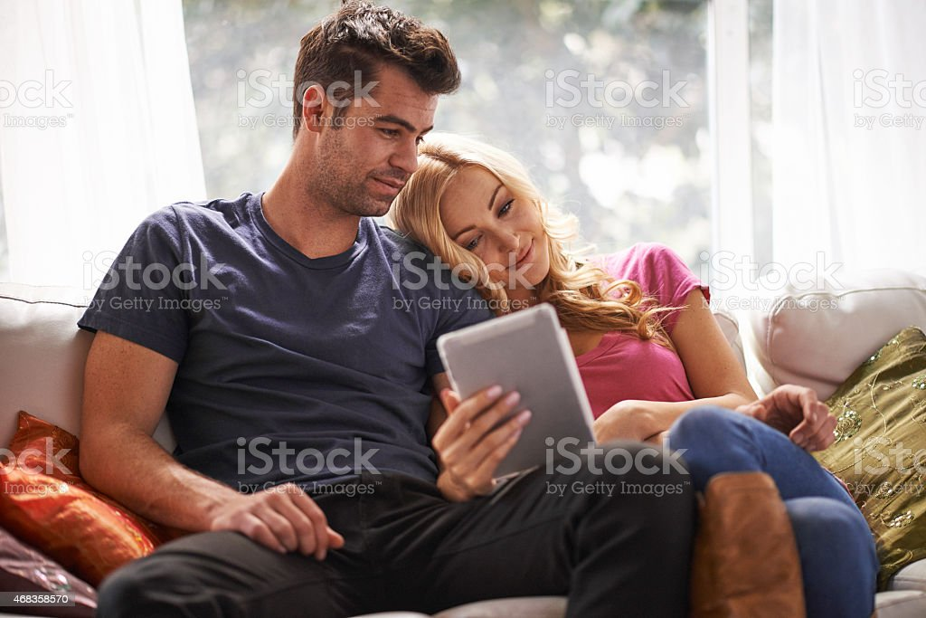 couple watching videos or shopping on tablet together royalty-free stock photo