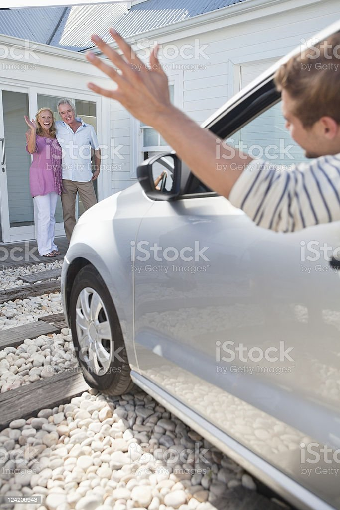 Couple waving goodbye to their son leaving in car royalty-free stock photo