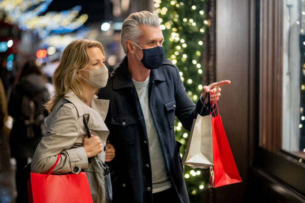 Couple wearing a facemask while Christmas shopping in London stock photo