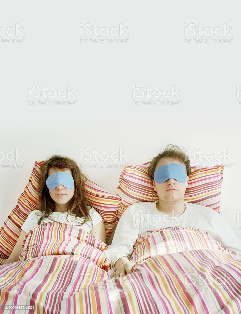 Couple wearing eye mask in bed foto de stock libre de derechos