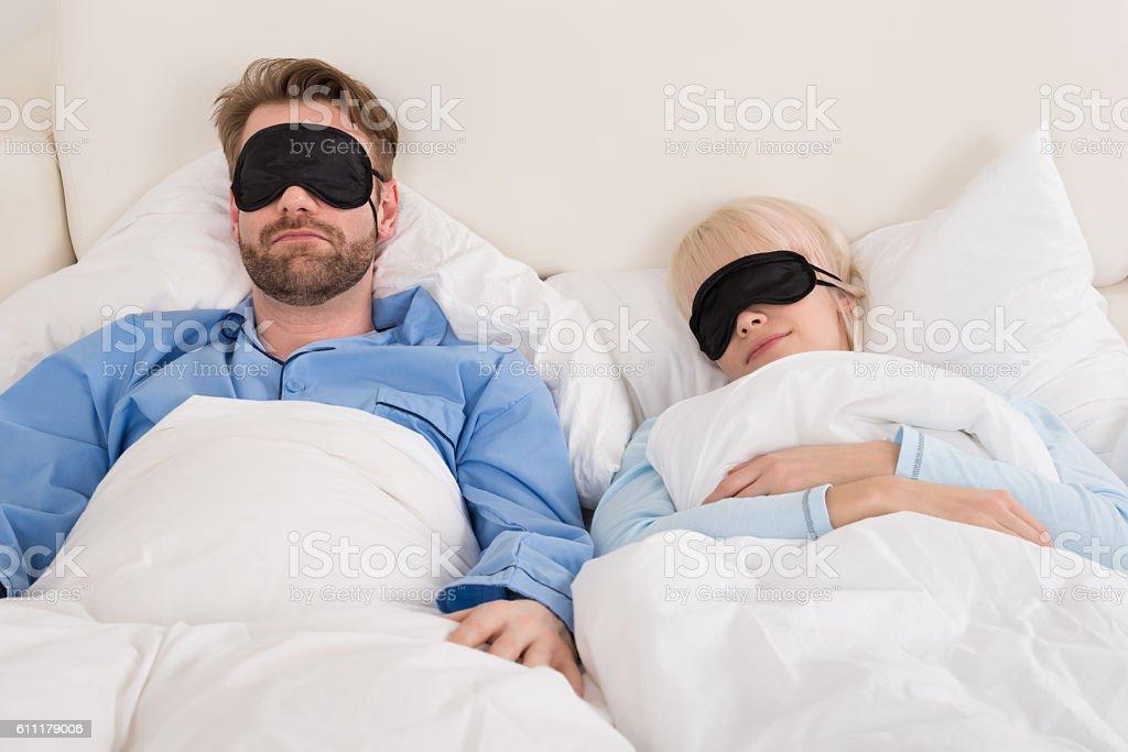 Couple Wearing Eyemask While Sleeping On Bed stock photo
