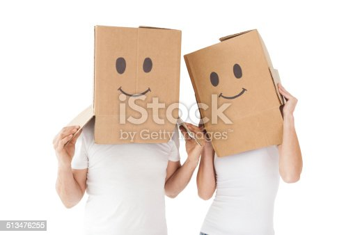 istock Couple wearing happy face boxes over heads 513476255
