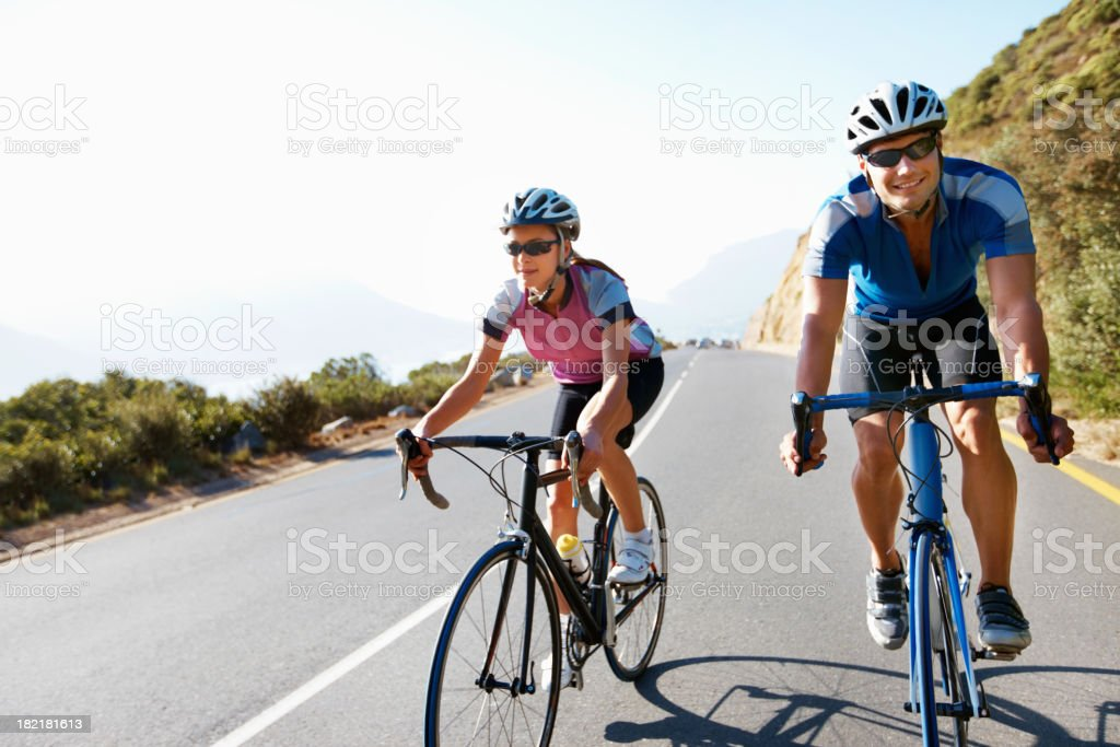 Couple wearing safety gear cycling on country road stock photo