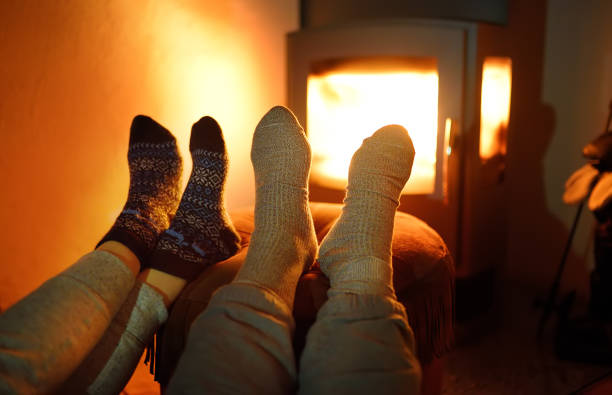 Couple wearing woollen socks near fireplace Couple wearing woollen socks near fireplace. Christmas eve concept. Winter holidays - Xmas and New Year. Cozy evening in the cold weather log fire stock pictures, royalty-free photos & images