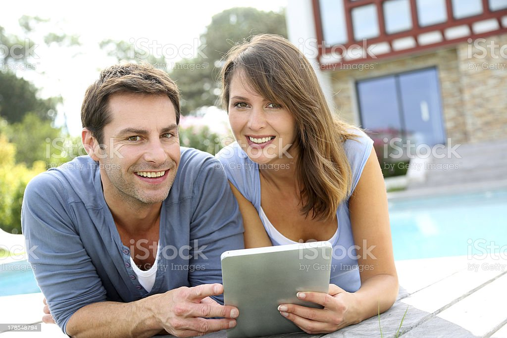 Couple websurfing on internet with tablet outside royalty-free stock photo