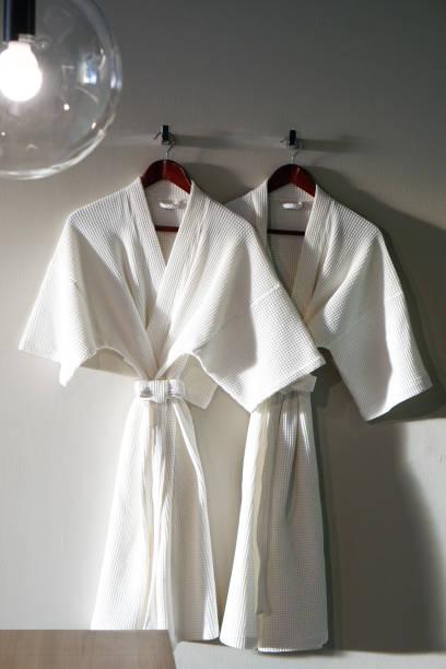 couple white bathrobe in wooden wardrobe - accappatoio foto e immagini stock