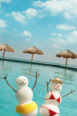 """""""Subject: A couple of male and female snowman and snow woman in swimsuit vacationing in a tropical beach pool.Location: Caribbean sea, Maya Riviera, Mexico."""""""