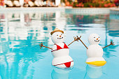 Subject: A snowman and snow woman tourist couple enjoying winter vacation in a tropical beach resort hotel.