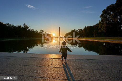 Couple with a Baby at the Lincoln Memorial with the Washington Memorial in the Background at Sunrise in Washington DC Capital of the USA