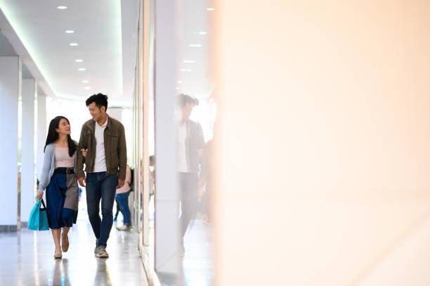 Paar mit Arm in Arm zu Fuß durch Läden – Foto