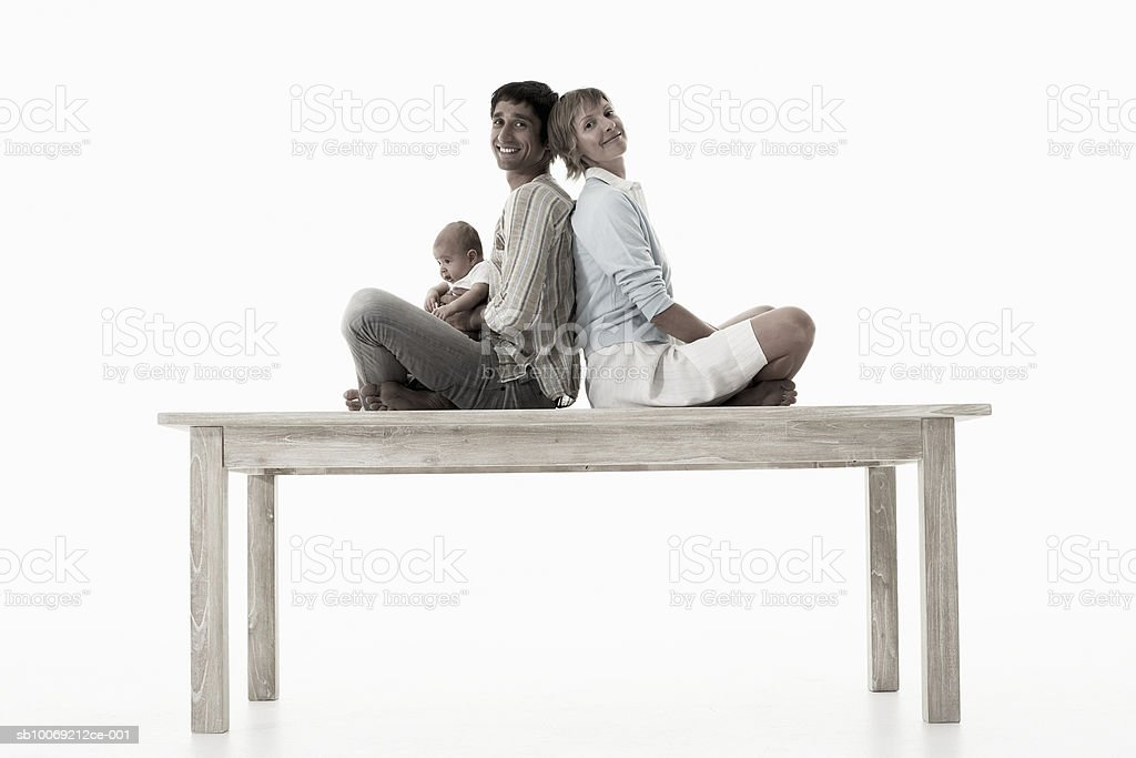 Couple with baby girl (2-5 months) sitting on table against white background, portrait royalty-free stock photo