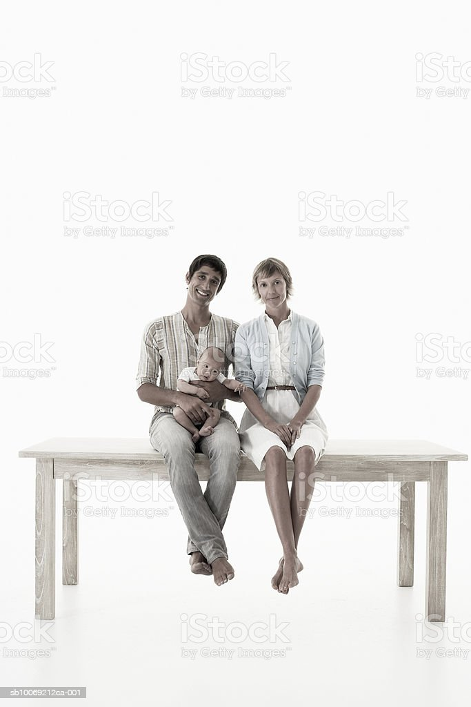 Couple with baby girl (2-5 months) sitting on wooden table against white background, portrait royalty-free stock photo