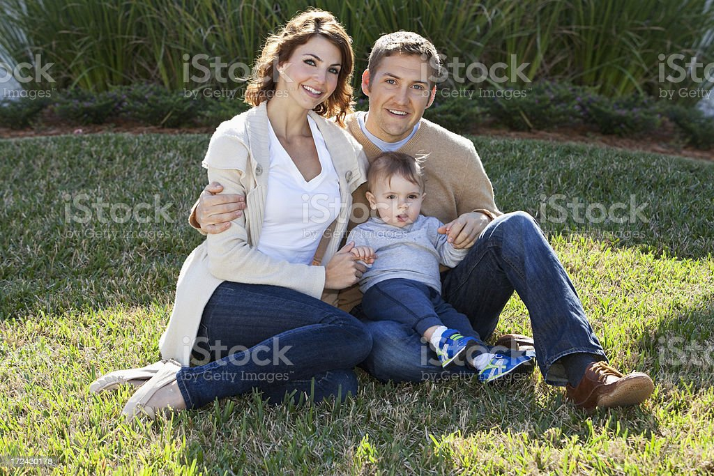 Couple with baby sitting outdoors stock photo