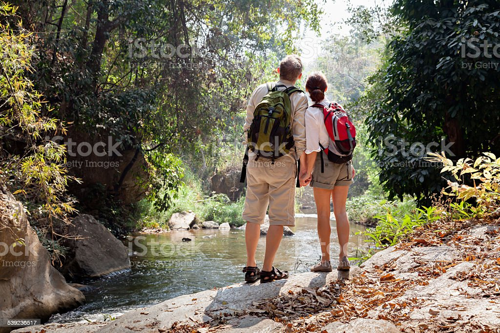 Couple with backpack hiking in rainforest royalty-free stock photo