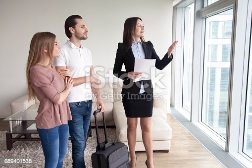 istock Couple with baggage rent apartment while travelling, meeting with broker 689401538