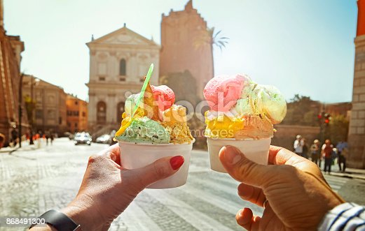 istock Couple with beautiful bright  sweet Italian ice-cream with different flavors  in the hands 868491300