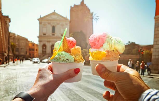 paar mit schönen hellen süß italienisches eis mit verschiedenen geschmacksrichtungen in den händen - italien stock-fotos und bilder