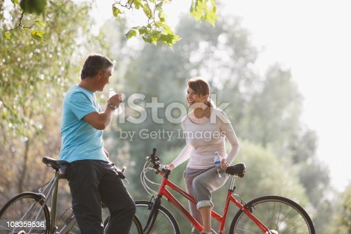 istock Couple with bicycles drinking water 108359536